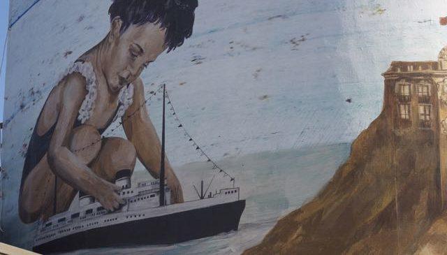 Una bambina gioca sulla riva del mare con una nave giocattolo che riproduce il Rex